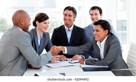 Happy business people closing a deal in a meeting