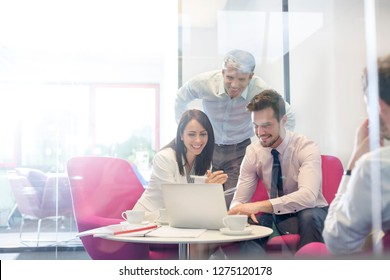 Happy business people discussing over laptop in office meeting