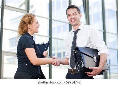 Happy business people greeting each other outdoors. Red-haired woman looking at her partner and having a handshake. Handsome man in business suit looking at the camera.