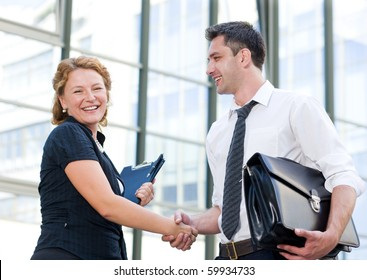 Happy business people having a handshake in front of office building. Red-haired woman big laughing and looking at the camera while holding contracts in her hand.