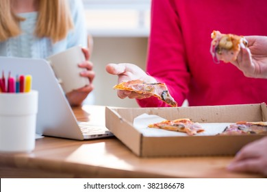 Happy business People Having Meeting And Eating Pizza in office.  Three young cheerful colleagues having lunch together at work. Creative team around table
