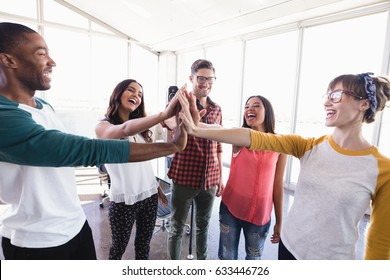 Happy business people high fiving while standing in office