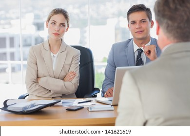 Happy business people interviewing business man in the office