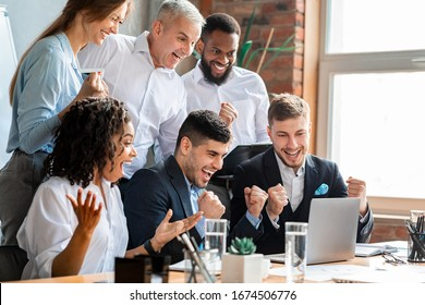 Happy Business People At Laptop Celebrating Success At Work Sitting In Modern Office. Successful Negotiations