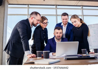 Happy business people looking at laptop presentation, success at work, sitting in modern office. Successful online negotiations. Businessmen share their knowledge