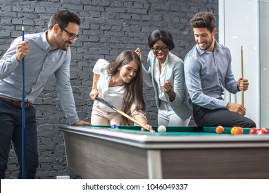 Happy business people playing billiards during office break.