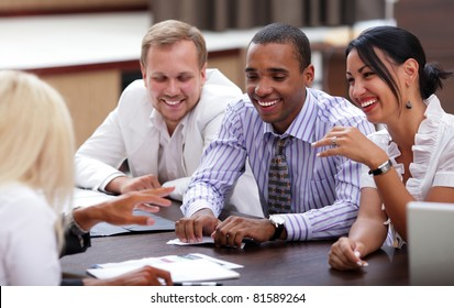 Happy business people sitting around the table at the meeting