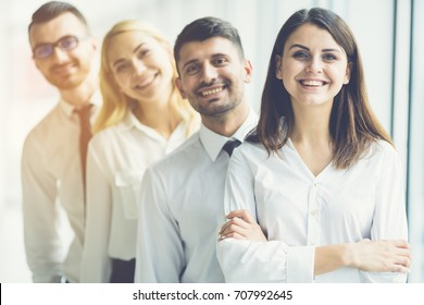 The happy business people stand on the sunny background