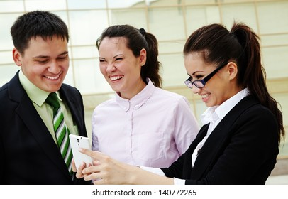 Happy business people standing and looking at mobile phone