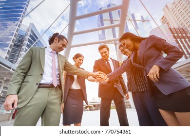 Happy Business people Teamwork Concept,Group of diversity people putting their hands together ,hand a young business people join hands partnership teamwork concept,city background