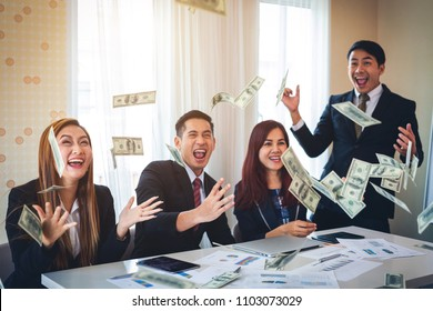 Happy business people are throwing dollar banknotes at office. Concept success of business
