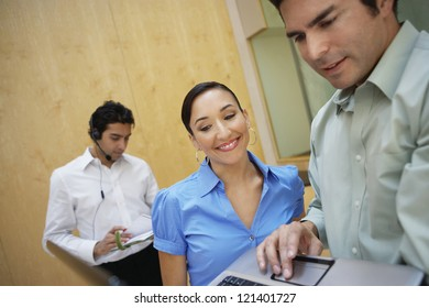 Happy business people using laptop with man wearing headset in the background