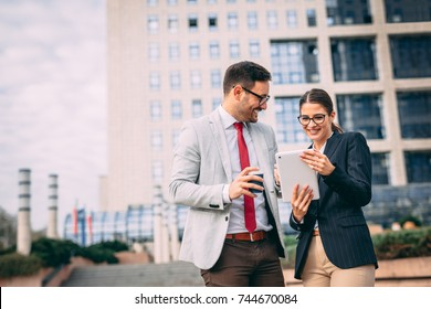 Happy business people working outside on tablet computer in front of tower building.