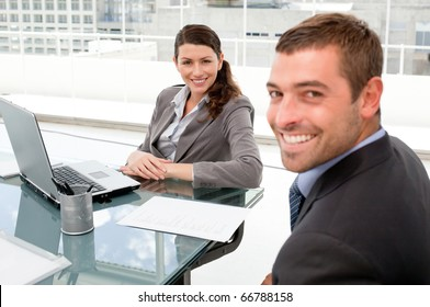 Happy business people working together on a laptop during a meeting