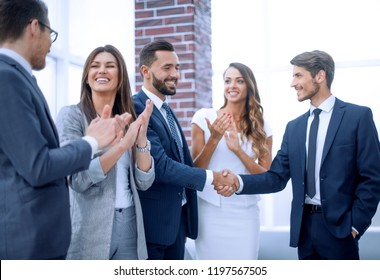 happy business team applauds new business partners