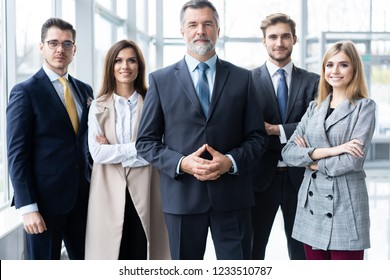 Happy business team with arms crossed at the office