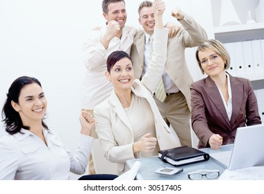 Happy business team celebrating success with arms raised, smiling.
