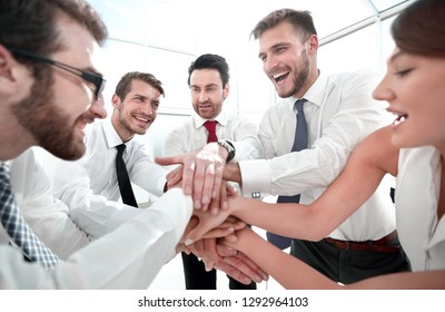 happy business team connects their hands together