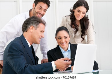 Happy business team discussing together at office meeting with laptop
