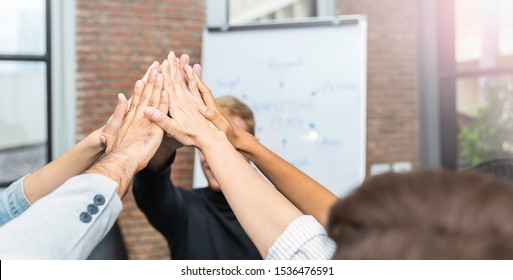 Happy business team giving high five in office with copy space. Hands of teamwork power winning and successful meeting workplace multicultural asian and caucasian concept banner