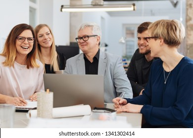 Happy business team laughing during a meeting as they all sit grouped around a man at a laptop at a table in the office
