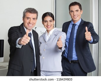 Happy business team in the office holding their thumbs up
