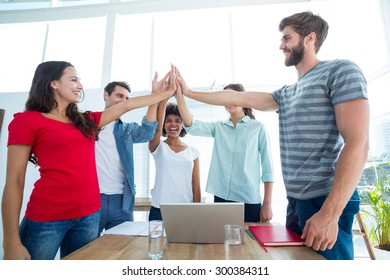 Happy business team putting their hands together in the office