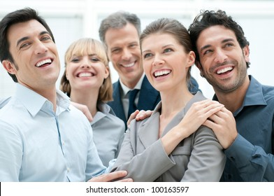 Happy business team smiling and laughing together at office