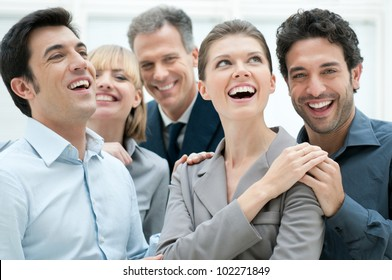 Happy business team smiling and laughing together at office to celebrate a success