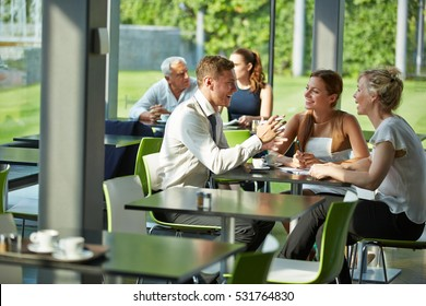 Happy business team talking and laughing together in a restaurant