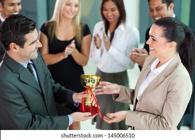happy business team winning a trophy