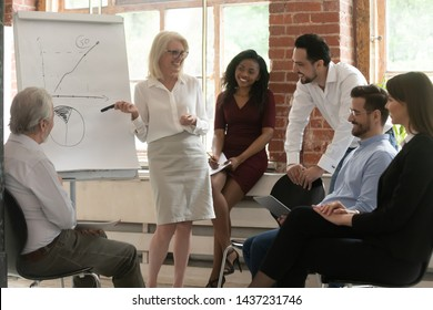 Happy business team young employees listen old mature female mentor give flip chart presentation in office, senior coach mentor teacher training multiracial interns workers group at corporate meeting