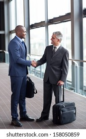 happy business travelers meeting at airport