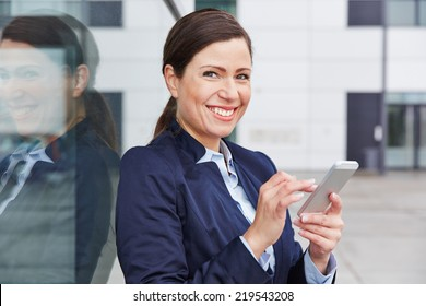 Happy business woman checking social media sites on her smartphone in the city