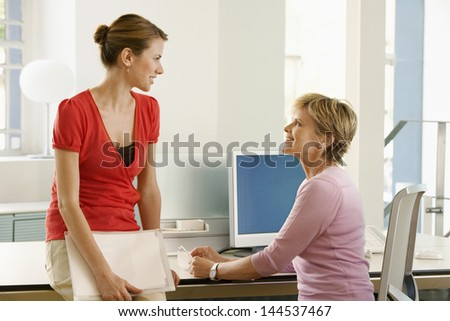 Happy business woman discussing at office desk