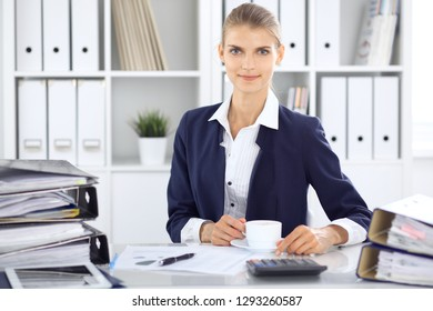 Happy business woman or female accountant having some minutes for coffee and pleasure at working place. Audit and tax concepts in business