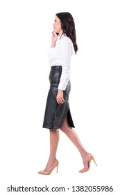 Happy business woman in formal clothes walking and talking on cellphone. Side view. Full body isolated on white background.