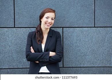Happy business woman with her arms crossed leaning on a wall