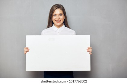 Happy business woman holding big white sign board. Gray wall back.