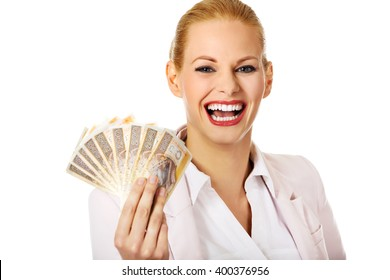 Happy business woman holding a clip of polish money