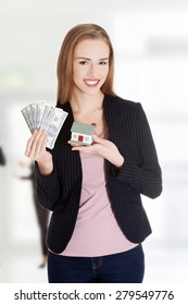 Happy business woman holding dollars and house.