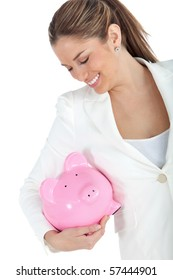 Happy business woman holding a piggybank - isolated over a white background