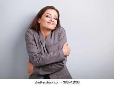 Happy business woman hugging herself with closed eyes and natural emotional face. Love concept of yourself