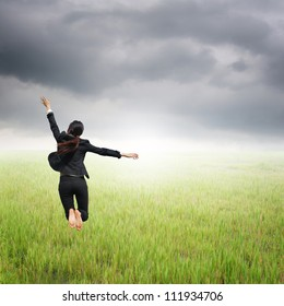 Happy Business woman jumping to raincloud in grassland