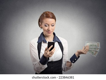 Happy business woman looking at smart phone throwing away cash dollar bills isolated grey wall background. Face expressions. Making spending money financial reward compensation concept