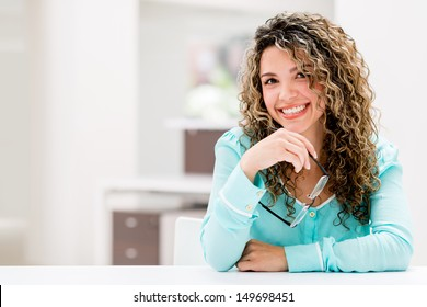 Happy business woman at the office smiling