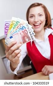 Happy business woman in office winning Euro money