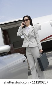 Happy business woman on a call standing by car with plane in the background at airfield