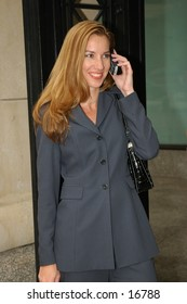 Happy business woman on cell phone in blue suit