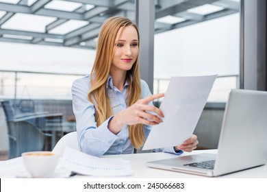 Happy business woman reading financial report